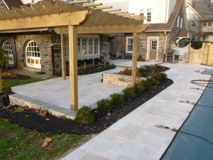 The final project featured a hardscaped patio and walls covered with Travertine pavers on all surfaces including the pool surround and a custom built pergola. (Image via aardweglandscaping.com – Main Line Philadelphia PA)