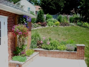Garden and patio with brick knee wall (By Aardweg Landscaping)